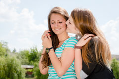 Duas meninas de sorriso que sussurram a bisbolhetice Fotografia de Stock Royalty Free