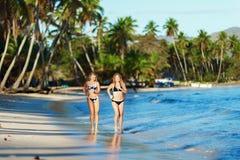 Duas meninas delgadas que correm na praia tropical arenosa Foto de Stock