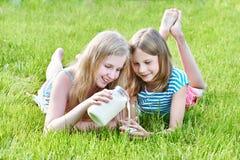 Duas meninas derramam o leite no prado ensolarado fotografia de stock royalty free