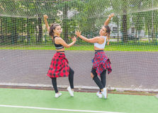 Duas meninas desportivas que levantam em uma grade do futebol no campo de jogos Fotos de Stock