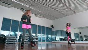 Duas meninas desportivas que saltam em sapatas do kangoo no gym filme