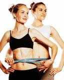 Duas meninas do esporte que medem-se isolaram-se no branco Imagem de Stock Royalty Free