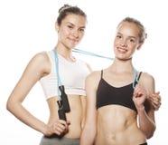 Duas meninas do esporte que medem-se isolaram-se sobre Fotos de Stock