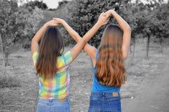 Duas meninas do melhor amigo que fazem um sinal do forever imagens de stock