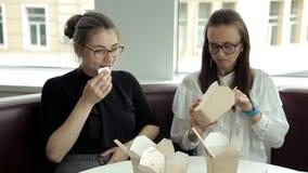 Duas meninas do negócio com os vidros que sentam-se em um café, comendo macarronetes chineses no almoço Alimento, café, ruptura n filme