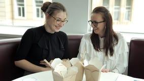 Duas meninas do negócio com os vidros que sentam-se em um café, comendo macarronetes chineses no almoço Alimento, café, ruptura n video estoque