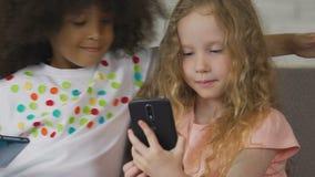 Duas meninas do pré-escolar que usam smartphones para gastar o tempo livre, as crianças e a tecnologia video estoque