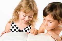 Duas meninas do preschooler que lêem um livro isolado Imagem de Stock