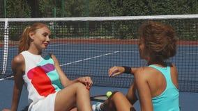 Duas meninas do tênis que falam ao relaxar na corte imagens de stock