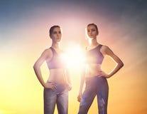 Duas meninas dos esportes no fundo do por do sol imagens de stock royalty free