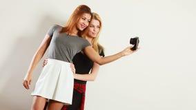 Duas meninas dos modelos que tomam a imagem do auto com câmera Fotos de Stock Royalty Free