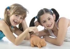 Duas meninas e banco piggy Fotos de Stock