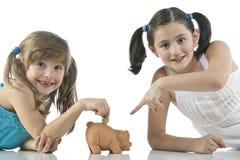 Duas meninas e banco piggy Fotografia de Stock