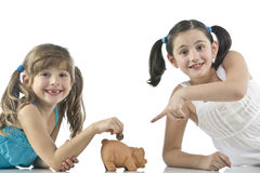 Duas meninas e banco piggy Fotos de Stock Royalty Free