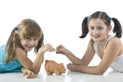 Duas meninas e banco piggy Foto de Stock