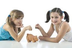 Duas meninas e banco piggy Imagem de Stock Royalty Free