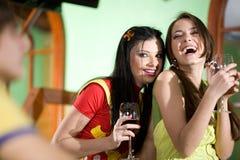 Duas meninas e o menino estão bebendo o vinho junto Imagens de Stock Royalty Free