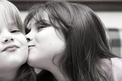 Duas meninas e um beijo Fotografia de Stock Royalty Free
