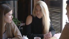Duas meninas e um homem novo que fala em um café que senta-se em uma tabela Bebem o chá e comem a pizza Dizem a notícia, eles video estoque