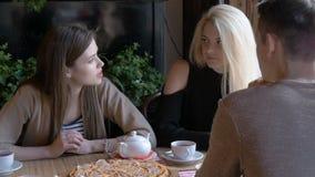 Duas meninas e um homem novo que fala em um café que senta-se em uma tabela Bebem o chá e comem a pizza Dizem a notícia, eles vídeos de arquivo