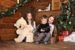 duas meninas e um rapaz pequeno estão sentando-se no assoalho contra uma parede de madeira fotografia de stock royalty free