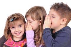Duas meninas e uma bisbilhotice do menino Imagem de Stock Royalty Free