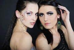 Duas meninas elegantes à moda bonitas aos modelos Imagens de Stock