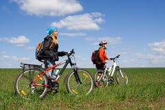 Duas meninas em bicicletas no campo. Fotografia de Stock