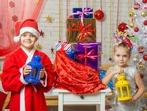 Duas meninas em trajes do Natal são com os castiçal do saco com presentes do Natal imagem de stock