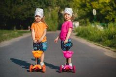 Duas meninas em 'trotinette's Imagens de Stock