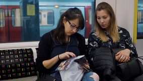 Duas meninas em um carro subterrâneo de Londres video estoque