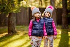 Duas meninas em um tampão e em um revestimento estão estando na grama em uma floresta do outono foto de stock