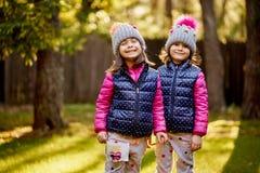 Duas meninas em um tampão e em um revestimento estão estando na grama em uma floresta do outono fotografia de stock