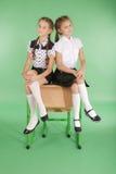 Duas meninas em uma farda da escola que senta-se na mesa imagem de stock royalty free