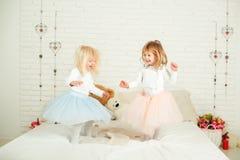 Duas meninas em vestidos agradáveis no divertimento que salta em uma cama foto de stock royalty free