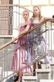 Duas meninas em vestidos bonitos nas escadas Fotos de Stock
