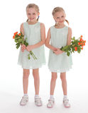 Duas meninas encantadores com os ramalhetes das rosas. Imagem de Stock
