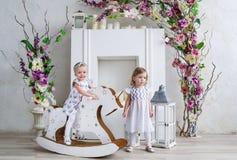 Duas meninas encantadores jogam na sala clara decorada com flores Bebê que balança em um cavalo de madeira Fotografia de Stock