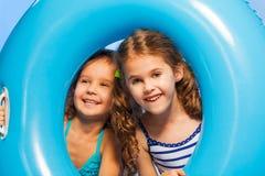 Duas meninas engraçadas no roupa de banho com anel de borracha grande Fotografia de Stock