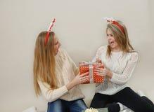 Duas meninas engraçadas que lutam sobre caixas de presente Fotos de Stock