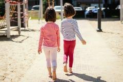 Duas meninas estão andando junto no campo de jogos imagem de stock