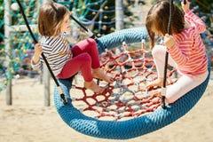 Duas meninas estão balançando em um balanço no campo de jogos Fotografia de Stock Royalty Free
