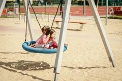 Duas meninas estão balançando em um balanço no campo de jogos Fotografia de Stock
