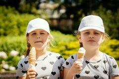 Duas meninas estão comendo o gelado no parque imagens de stock royalty free