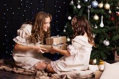 Duas meninas estão compartilhando de presentes perto da árvore de Natal fotografia de stock
