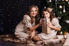 Duas meninas estão compartilhando de presentes perto da árvore de Natal imagens de stock royalty free