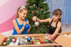 Duas meninas estão considerando bolas em uma caixa com os brinquedos de ano novo fotografia de stock
