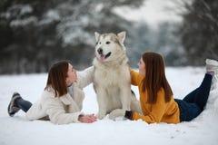 Duas meninas estão encontrando-se na neve ao lado de um Malamute do Alasca do cão e abraçam o seu foto de stock royalty free