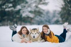 Duas meninas estão encontrando-se na neve ao lado de um Malamute do Alasca do cão e abraçam o seu fotos de stock royalty free