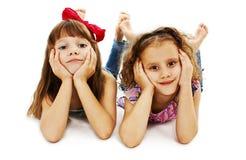 Duas meninas estão encontrando-se no assoalho Imagens de Stock Royalty Free